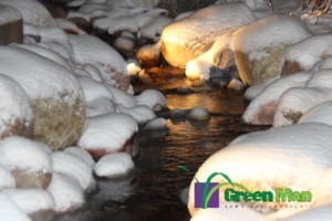 Landscape installation featuring a water feature at night covered in snow