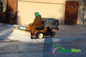 Sidewalk plow providing snow removal services